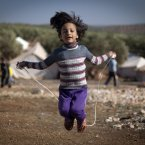 7 November: A Syrian girl who fled with her family from the violence in their village, jumps a rope at a displaced camp, in the Syrian village of Atma. (AP Photo/ Khalil Hamra)