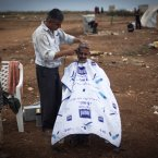 8 November: A Syrian man who fled from the violence in his village, sits for a haircut next to his tent at a camp in the Syrian village of Atmeh, near the Turkish border. (AP Photo/Khalil Hamra)