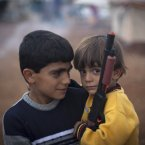 8 November: Two Syrian boys who fled with their families from the violence in their village, look on as one holds a gun toy at a displaced camp, in the Syrian village of Atmeh, near the Turkish border. (AP Photo/ Khalil Hamra)