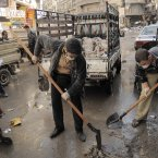 10 November: Activists collect garbage from the streets of Aleppo.  Three months after the war broke out in the city, street cleaning and garbage pickup services collapsed because of fighting and shelling. (AP Photo/MÃnica G. Prieto)