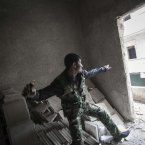 7 December: A rebel fighter throws a grenade toward Syrian troops loyal to President Bashar Assad during clashes in Aleppo. (AP Photo/Narciso Contreras)