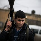 10 December: A very young-looking FSA fighter holds his weapon as he prepares himself for advance, close to a military base, near Azaz. (AP Photo/Manu Brabo)