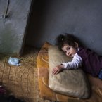 30 September: Rada Hallabi, 4, who is sick with diabetes, lies on a blanket in a refugee camp on the border with Turkey. (AP Photo / Manu Brabo)