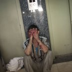 4 October: A Syrian man cries in a hallway of the Dar El Shifa hospital in Aleppo, Syria after his daughter was hit during a Syrian Air Force strike over a school where hundreds of refugees had taken shelter. (AP Photo/ Manu Brabo)