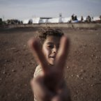7 October: A Syrian girl flashes the victory sign at a refugee camp in Azaz, near the Turkish border. (AP Photo/ Manu Brabo)