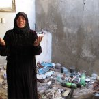 5 August: Fatoum Obeid, 50, stands in a pile of trash left by Syrian soldiers who occupied her home in Atarib, Syria. (AP Photo/Ben Hubbard)