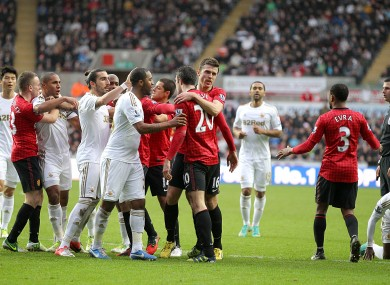 Match referee Michael Oliver (right) looks on as a melee on the pitch erupts during a confrontation between Swansea City's Ashley Williams (third left) and Manchester United's Robin van Persie (centre right).