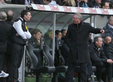 Manchester United manager Sir Alex Ferguson (right) speaks with fourth official Lee Probert (left) on the touchline.