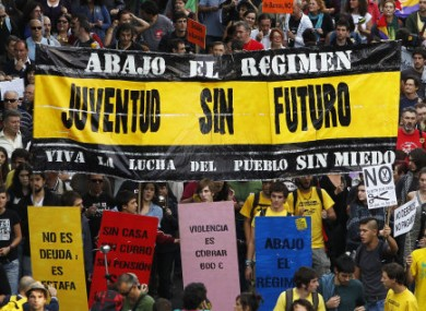 Protesters march in Madrid and hold banners reading, 'A youth with no future'.