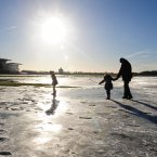 People walk on the remaining frozen flood water on York Racecourse (Anna Gowthorpe/PA Wire)
