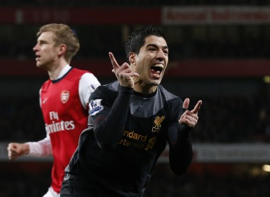 Liverpool's Luis Suarez, right, celebrates his goal as Arsenal's Per Mertesacker stands in the background during the Premier League match between Arsenal and Liverpool.