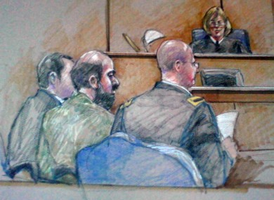 In this courtroom sketch, Nidal Hasan is seen sitting between members of his defence team during a hearing in Fort Hood