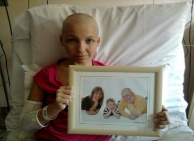 Marta Salacka in her hospital bed holding a picture of her family.