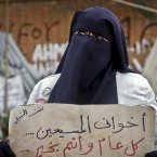 An Egyptian woman holds a poster that reads: