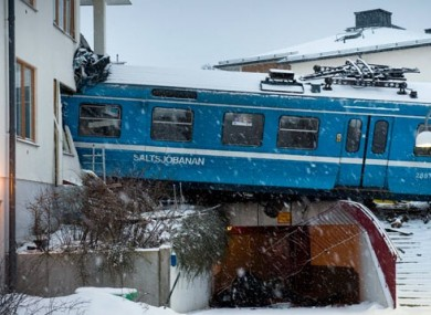 The derailed train hangs on the edge of the track after it crashed into the side of a residential building in Saltsjobaden outside Stockholm, Sweden.