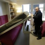 Jack Sproule tries out a fold-down bed in the model apartment. (AP Photo/Seth Wenig)