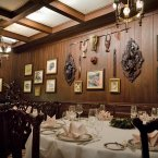 The Trophy Room is the slightly more informal dining room, with sketches and masks bedecking the wood-planked walls.