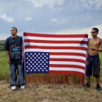 Oglala youths hold an upside-down flag, an international symbol of distress and an act of defiance toward the US government, at a rally to commemorate the 1975 shoot-out between American Indian Movement (AIM) activists and FBI agents. Two agents and one AIM member died. The image was taken at the Pine Ridge Indian Reservation in South Dakota. (Image: Aaron Huey) 